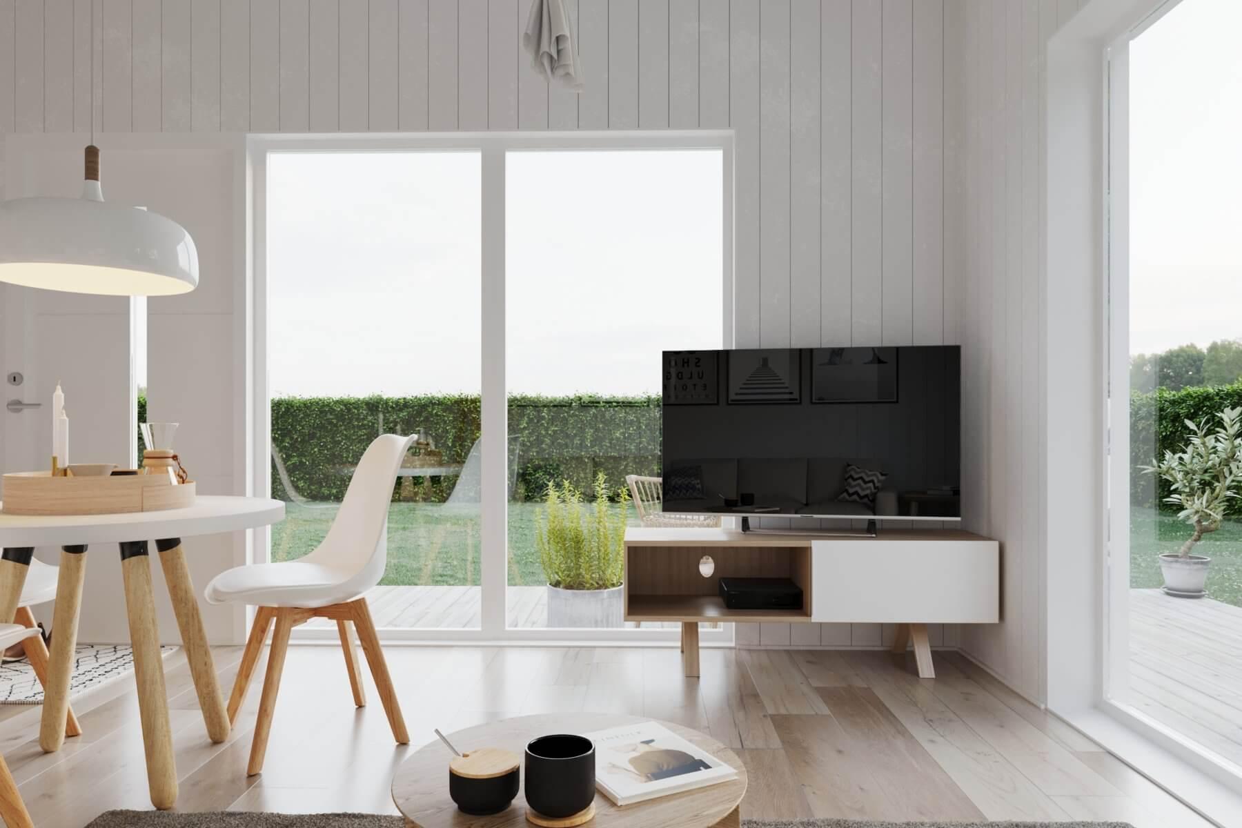 Vardagsrum i attefallshus med tv stående på tv-bänk och vackra panoramafönster