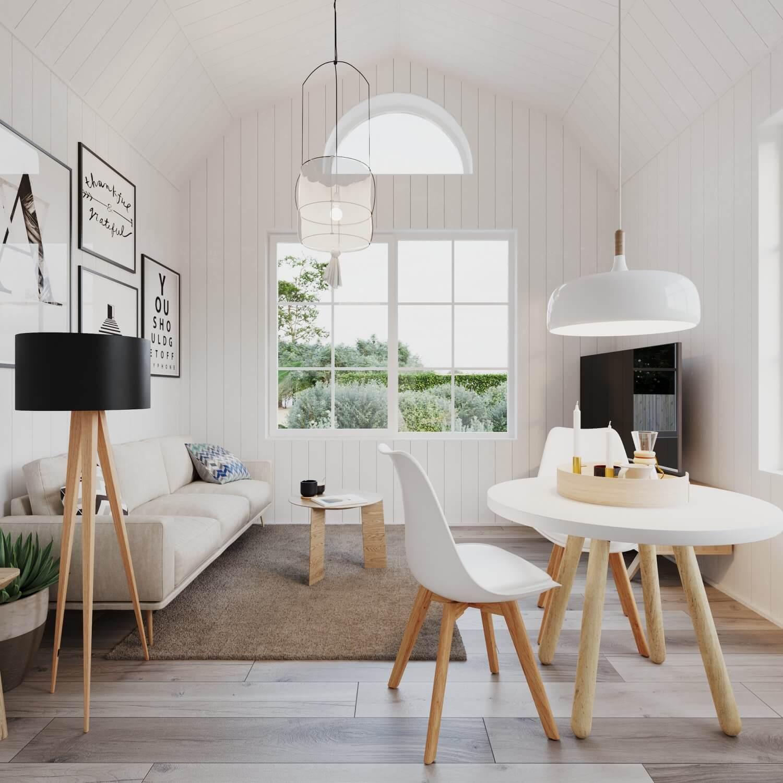 Vardagsrum med soffa, soffbord och tv i attefallshus med mansardtak