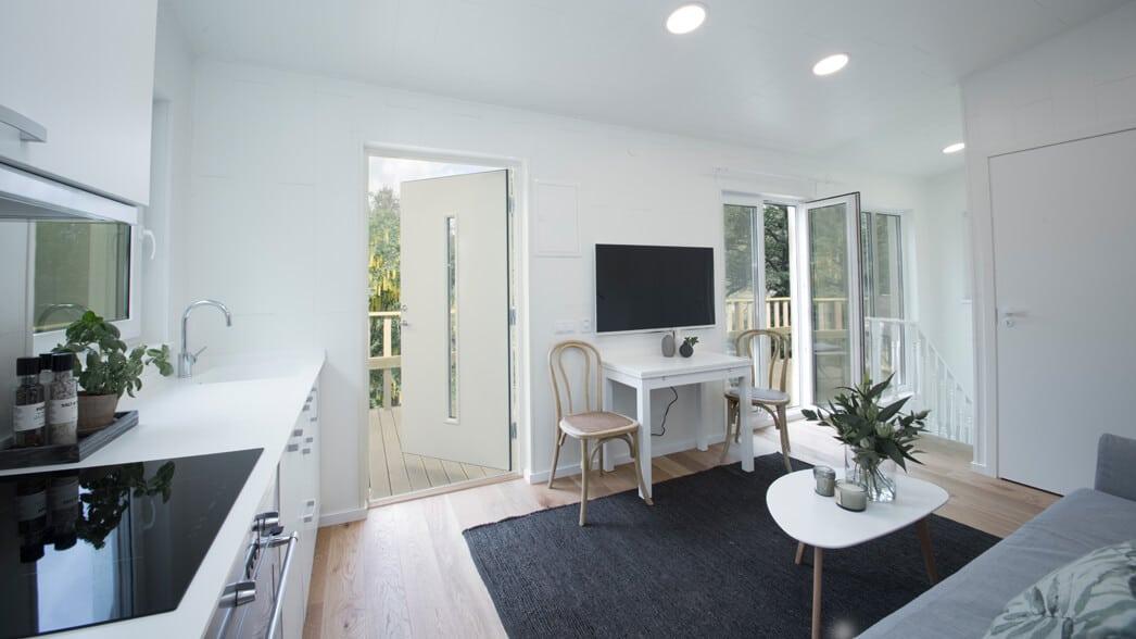 Kombinerat kök och vardagsrum med öppen ytterdörr