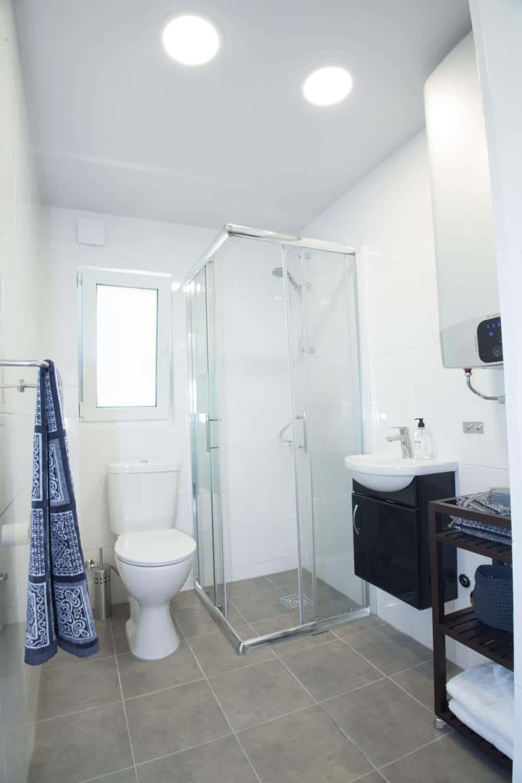 Ljust badrum med glasdörrar till dusch