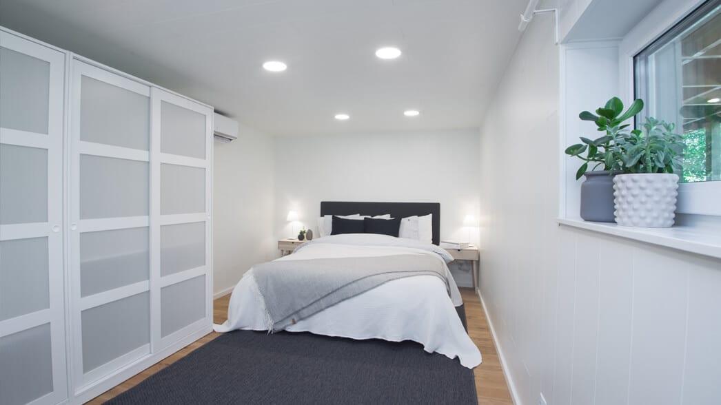 Sovrum med dubbelsäng och spotlights i taket