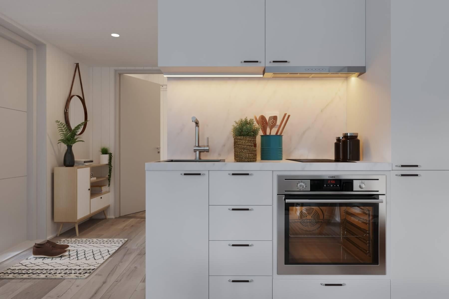 Kök med ugn, induktionshäll, förvaring och tänd belysning i fritidshus