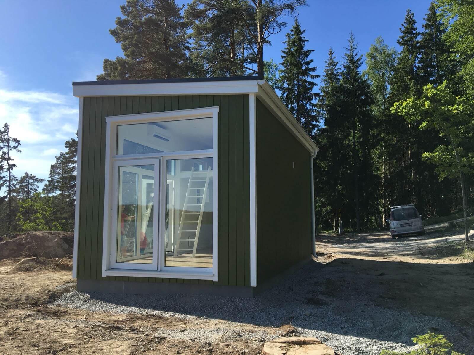 Grönt Attefallshus med pulpettak och panoramafönster
