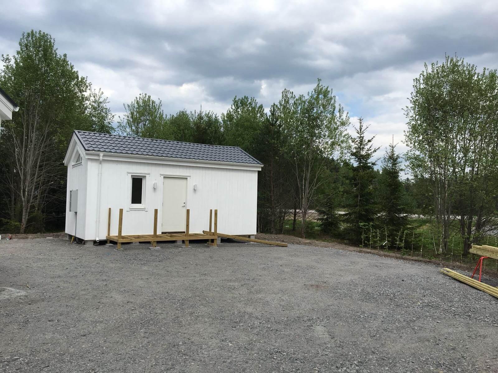 Vitt Attefallshus med svart tak