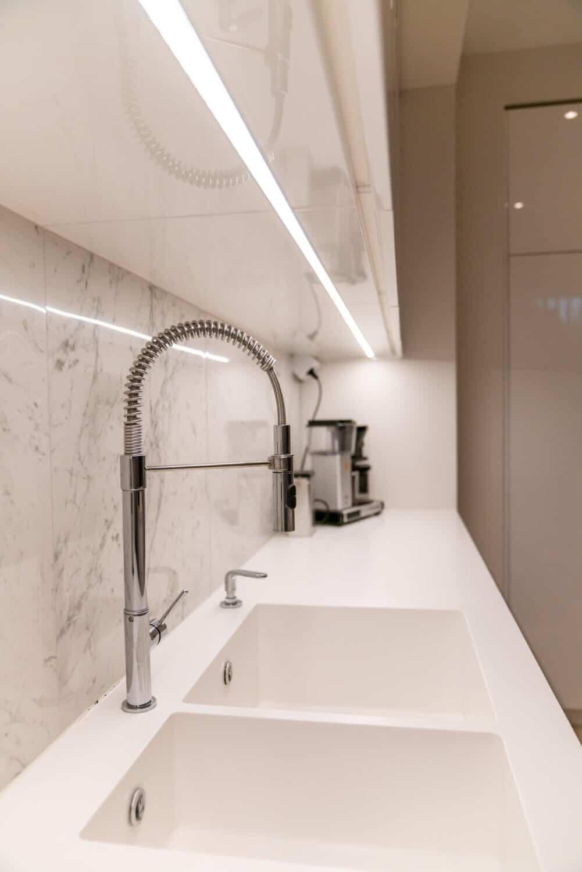 Anpassad kök med stänkskydd i marmor och bänkskiva i Corian
