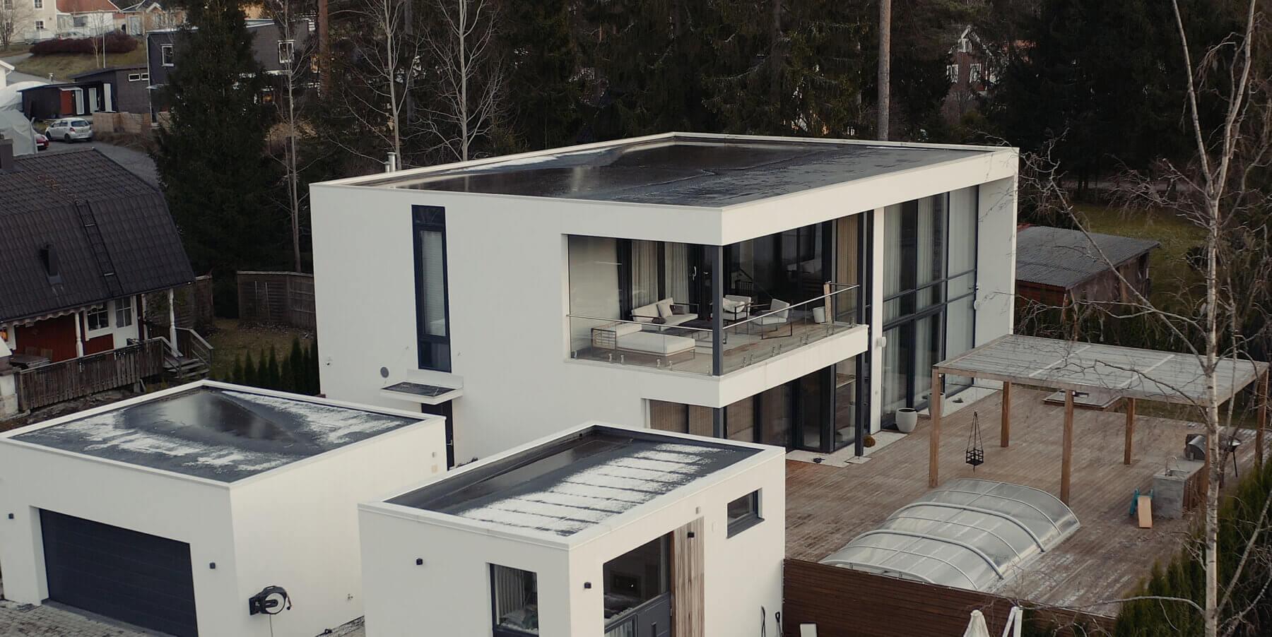 Arkitektritat hus med putsad fasad och cederträ detaljer