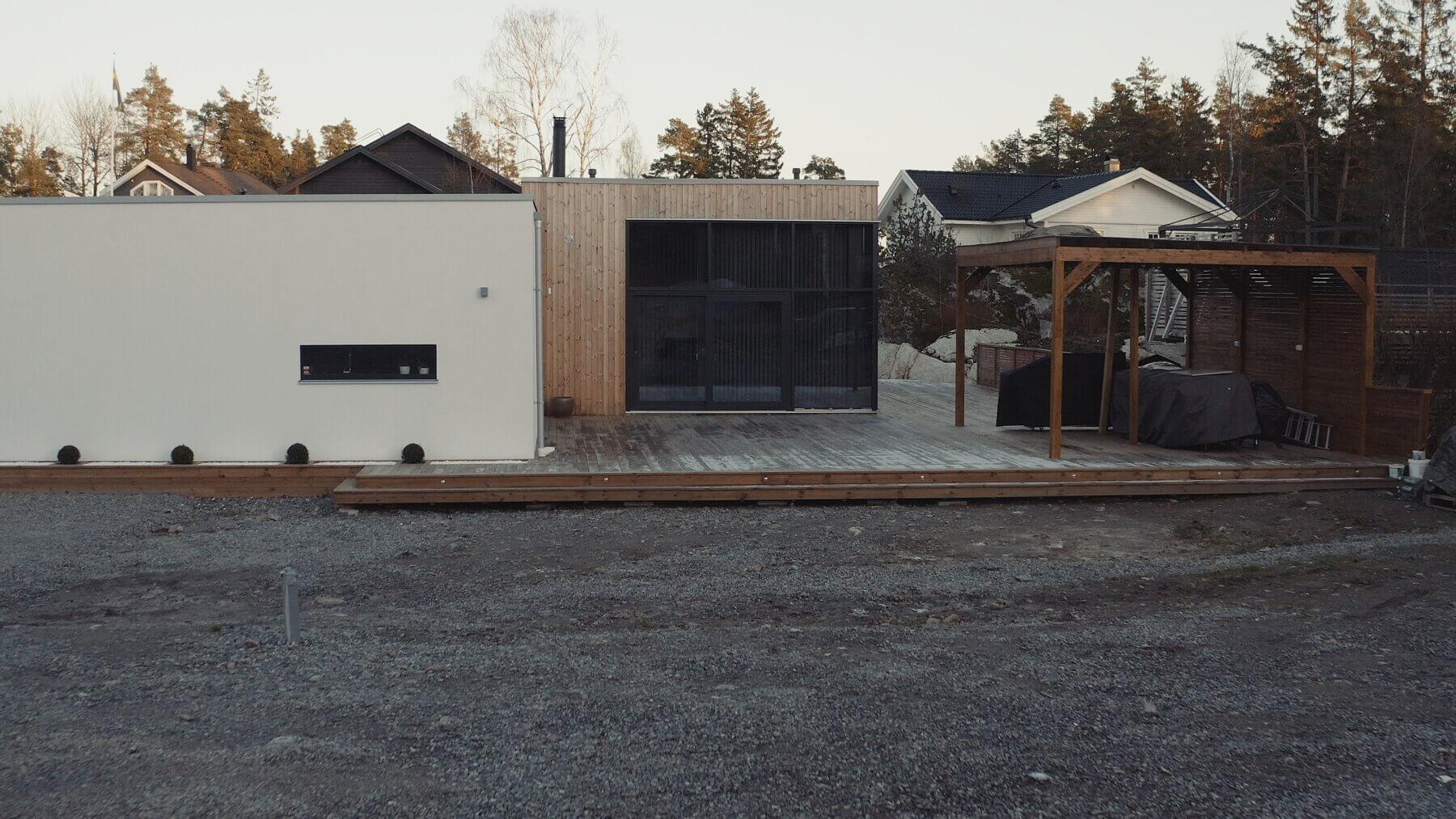 Arkitektritat modulhus med putsad fasad och thermowood panel